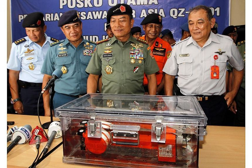 The Commander of the Indonesian Armed Forces (TNI), General Moeldoko (2nd from right), poses for journalists behind the rocovered flight data recorder during a press conference at the Iskandar Military Airport in Pangkalan Bun, Central Borneo, Indone