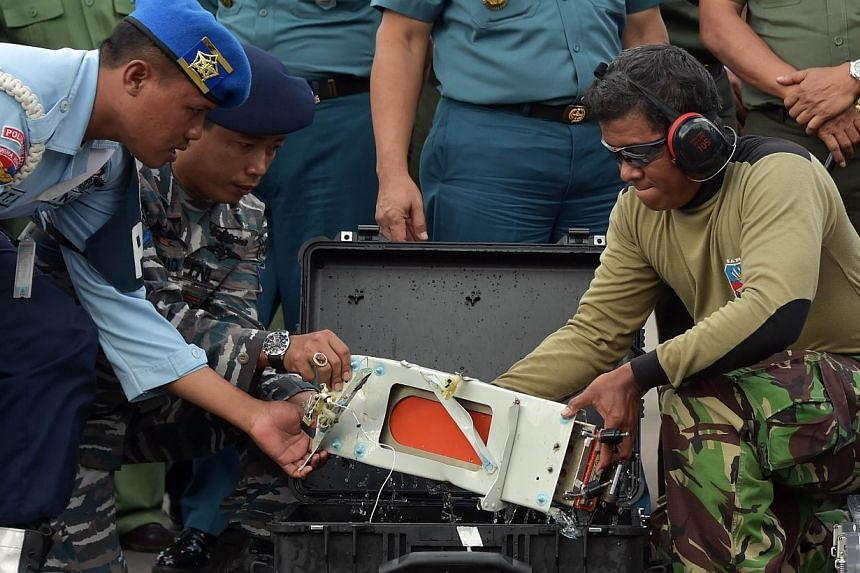 Indonesian officers move the FDR (Flight Data Recorder) of AirAsia flight QZ8501 into a suitable protective transportation case in Pangkalan Bun after it was retrieved from the Java Sea on Jan 12, 2015.-- PHOTO: AFP