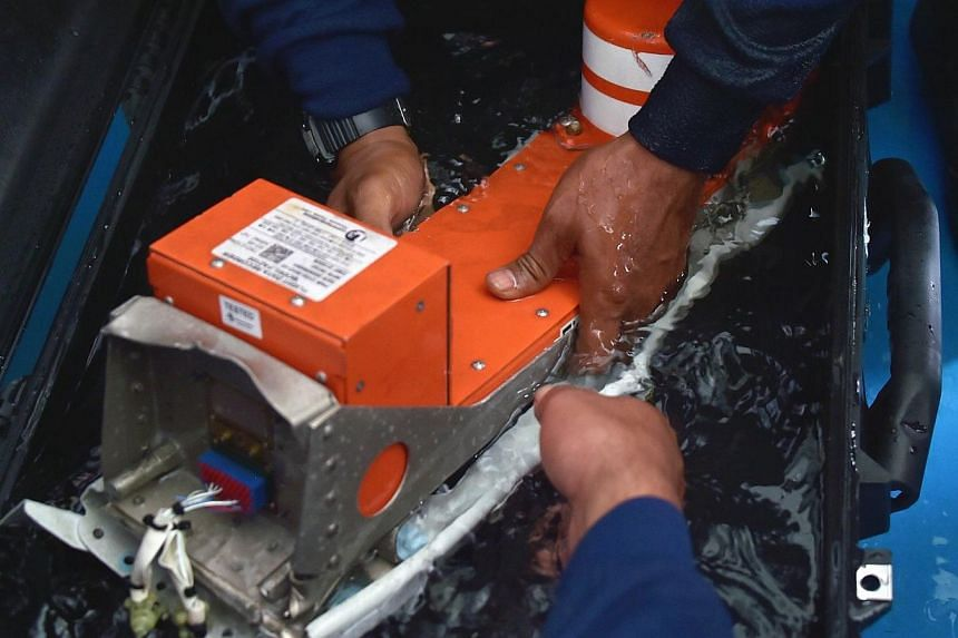 Indonesian divers onboard the Indonesian navy vessel KRI Banda Aceh handle the FDR (Flight Data Recorder) of the AirAsia flight QZ8501 after it was retrieved from the Java Sea on Jan 12, 2015.-- PHOTO: AFP