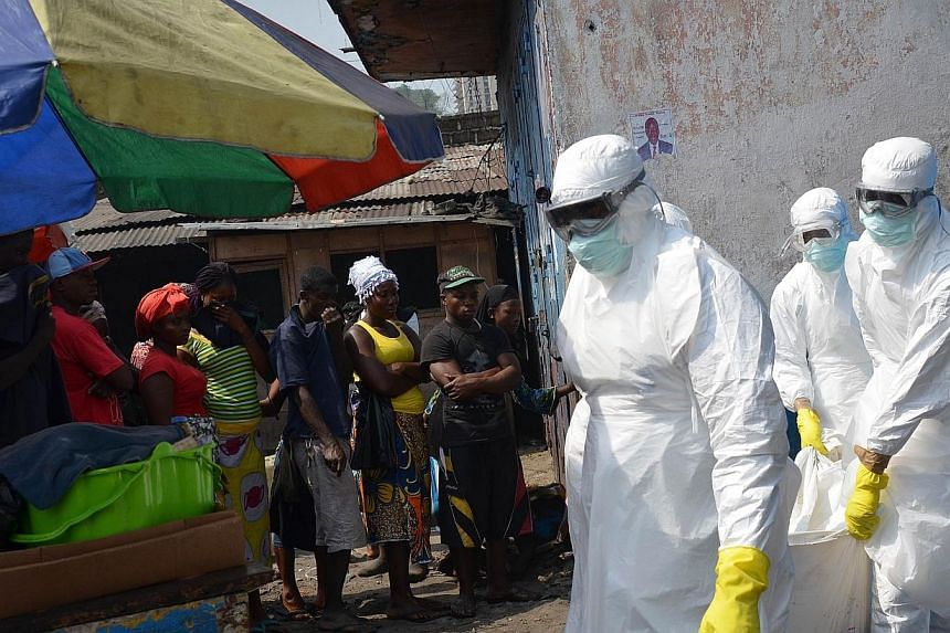Red cross workers, wearing protective suits, carry the body of a person who died from Ebola during a burial with relatives of the victims of the virus, in Monrovia, on Jan 5, 2015.China has been quietly toughening travel restrictions on student