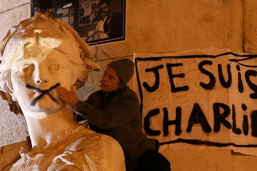 """A man touching the mouth of a statue that had been spray-painted shut near a poster reading """"I am Charlie"""" as he takes part in a solidarity march (Marche Republicaine) in the streets of Paris on Jan 11, 2015.Blanket news coverage around the wor"""