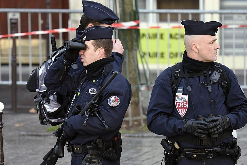"""Police security forces watch over the Unity rally """"Marche Republicaine"""" on Jan 11, 2015 in Paris in tribute to the 17 victims of the three-day killing spree.France will deploy nearly 5,000 security forces and police personnel to protect the"""