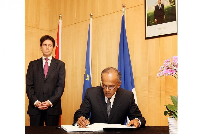 """Foreign Affairs and Law Minister K Shanmugam signing a condolence book for victims of the Paris terror attacks at the French Embassy on Cluny Road.The """"barbaric"""" terrorist attacks in Paris last week were the acts of """"sick and mad people"""" and ha"""