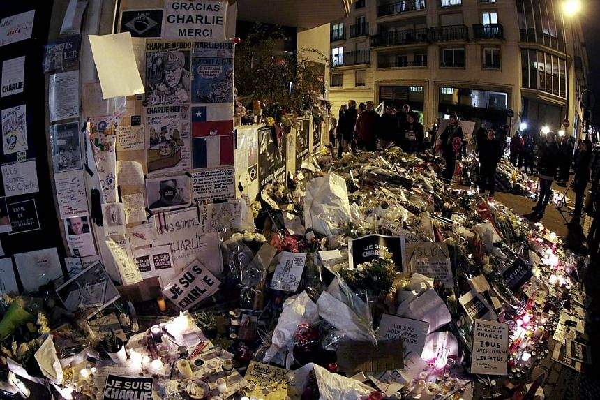 """People visit a makeshift memorial near the headquarters of the French satirical weekly Charlie Hebdo at the end of the unity rally """"Marche Republicaine"""" on Jan 11, 2015 in Paris. A veteran Algerian militant and former Al-Qaeda fighter, Mokhtar Belmok"""