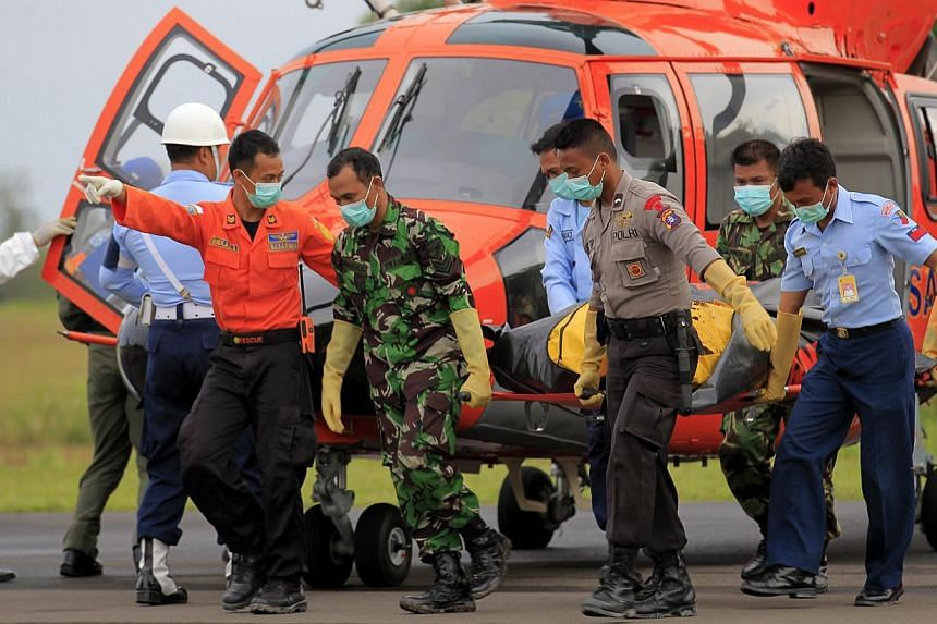 Members of the Indonesian national search and rescue agency (BASARNAS) carry the body of a victim of a crashed AirAsia plane at Iskandar Military Airport in Pangkalan Bun, Central Borneo, Indonesia on Jan 9, 2015.-- PHOTO: EPA
