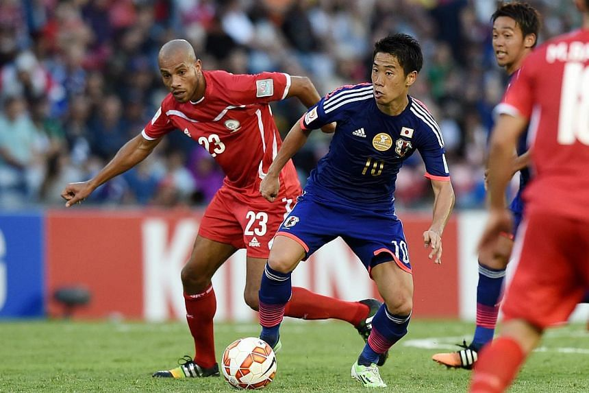 Shinji Kagawa of Japan, (right), is challenged by Murad Said of Palestine during the Group D Asian Cup match at Newcastle Stadium in Newcastle, Australia, on Jan 12, 2015. Japan kicked off their Asian Cup title defence with a 4-0 victory over As