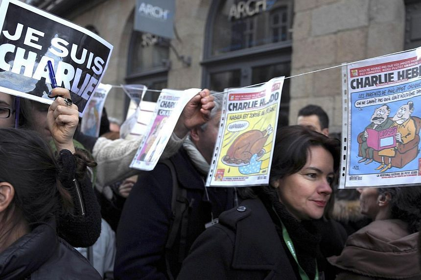 People walk by frontpages of Charlie-Hebdo magazines during in a unity rally (Marche Republicaine) on Jan 11, 2015, in Rennes where some 115,000 people took part in tribute to the 17 victims of the three-day killing spree. -- PHOTO: AFP
