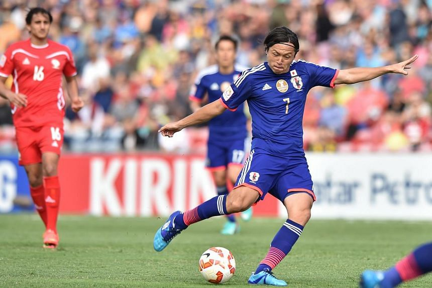 Yasuhito Endo of Japan (centre) shoots to score a goal against Palestine during their Group D football match of the AFC Asian Cup in Newcastle on Jany 12, 2015. An early 30-metre strike by Endo set Japan's Asian Cup title defence off to the perf