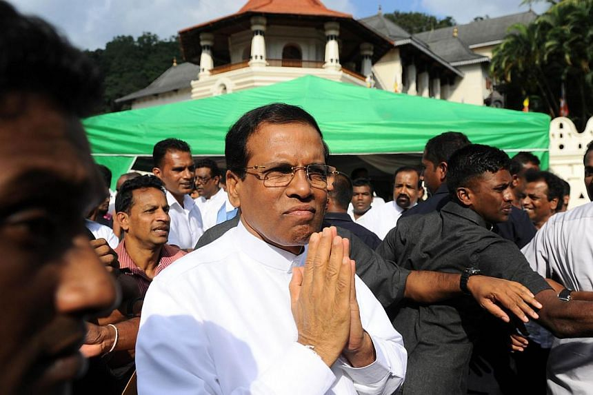 New Sri Lankan President Maithripala Sirisena gestures to supporters after speaking outside of the Buddhist Temple of Tooth in the central town of Kandy on Jan 11, 2015. Sri Lanka's new president has axed hundreds of officials and diplomats appo