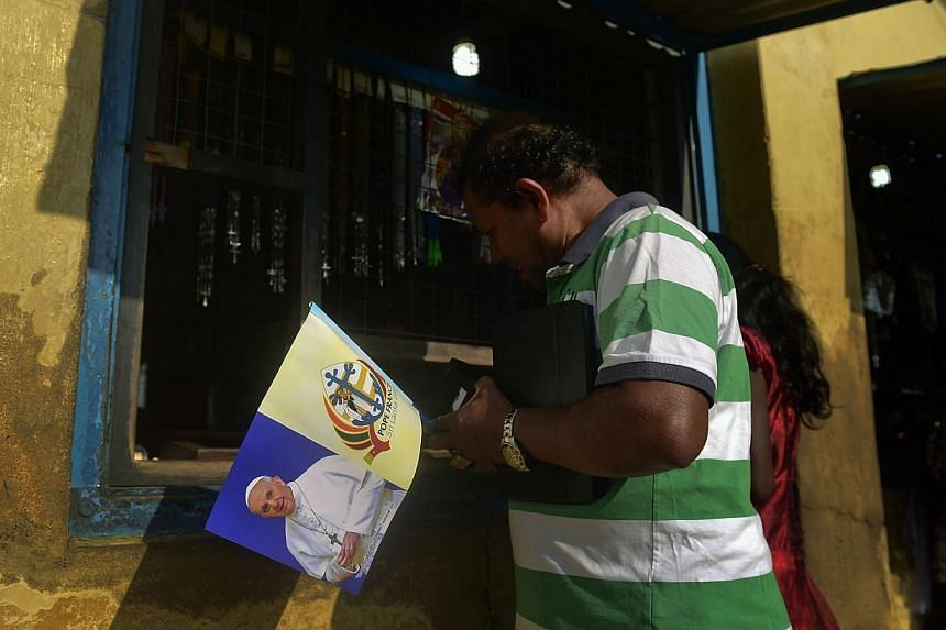 In a picture taken on Jan 11, 2015, a Sri Lankan Christian buys a souvenir flag ahead of Pope Francis' visit in Madhu. -- PHOTO: AFP