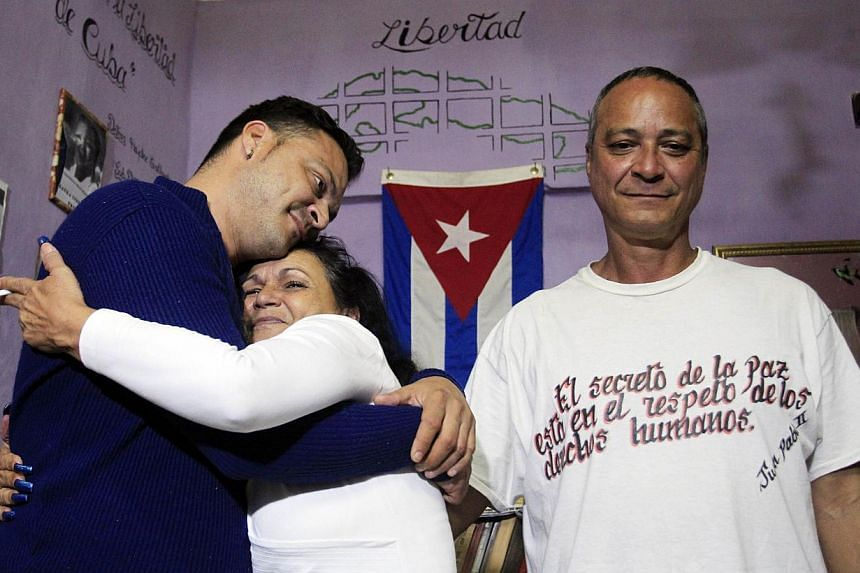 Angel Figueredo (right) stands next to his wife Haydee Gallardo who hugs their son Reynier at their home in Havana, on Jan 8, 2015. Cuba has released all 53 political prisoners it agreed to free as part of a historic deal with the United States annou