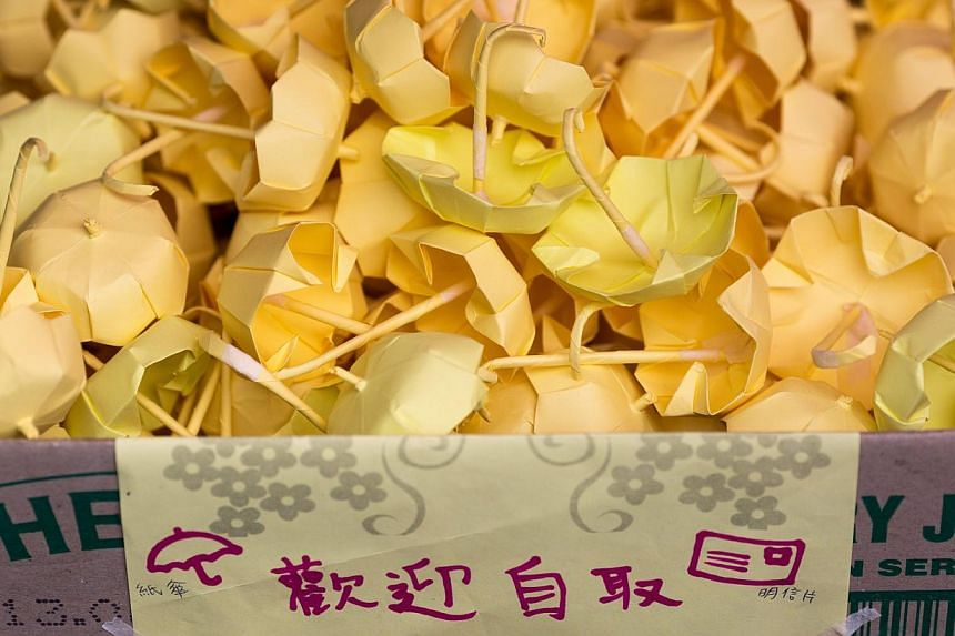 Paper yellow mini umbrellas sit in a box as they are given away by protesters outside the Legislative Council building in Hong Kong, China, on Jan 7, 2014.-- PHOTO: EPA