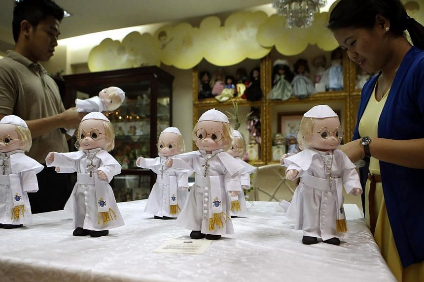 Shop workers arrange miniature Pope Francis dolls, which measure 12-inches (30cm) in height, at a gift shop in Makati, Metro Manila on Jan 12, 2015. -- PHOTO: REUTERS