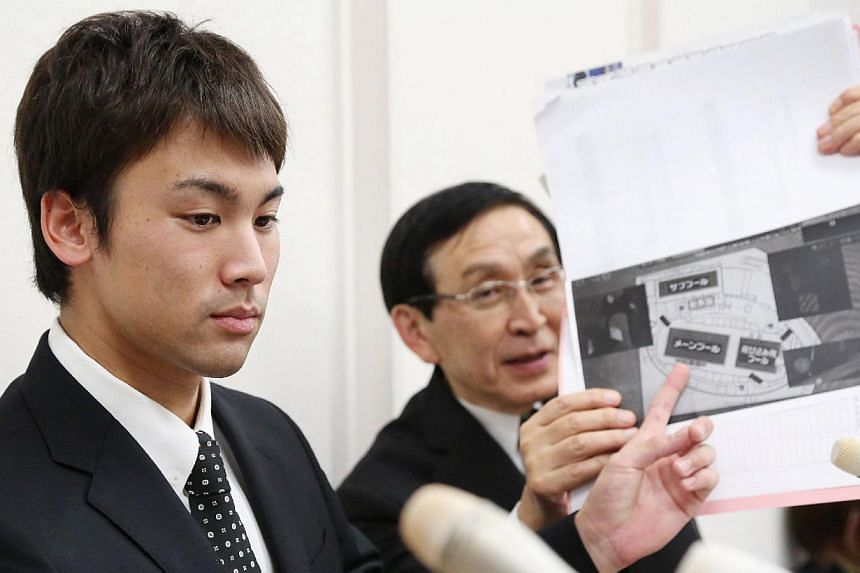 Japanese swimmer Naoya Tomita (left) points at a map of the swimming venue at the Asian games as he speaks to the press in Nagoya in Aichi prefecture, central Japan on Nov 6, 2014, as he denied he had stolen a journalist's camera at the Asian Games i