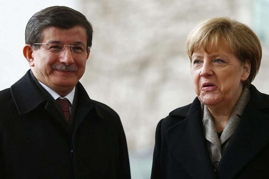 German Chancellor Angela Merkel reacts next to Turkish Prime Minister Ahmet Davutoglu during a welcoming ceremony in Berlin, on Jan 12, 2015.-- PHOTO: REUTERS