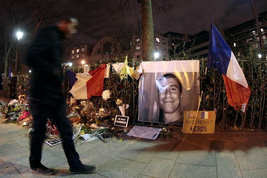 "A man walking past a makeshift memorial for French policeman Ahmed Merabet near the site where he was shot dead by gunmen close to the headquarters of the French satirical weekly Charlie Hebdo at the end of the unity rally ""Marche Republicaine"" on Ja"