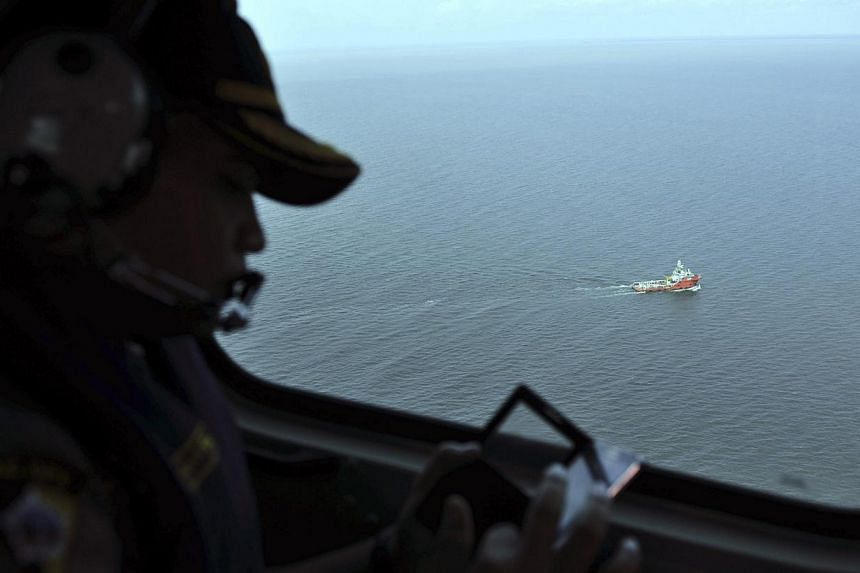 An Indonesian policeman watches from the air as the search operation in the Java sea goes underway. Indonesia's search and rescue agency said on Monday morning that search teams had managed to get part of the flight data recorder of the Indonesia Air