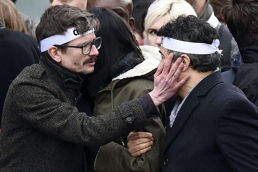 "Luz (left) touching the face of Dr Patrick Pelloux as they and members of the Charlie Hebdo satirical magazine team take part in a unity rally ""Marche Republicaine"" on Jan 11, 2015 in Paris. -- PHOTO: AFP"