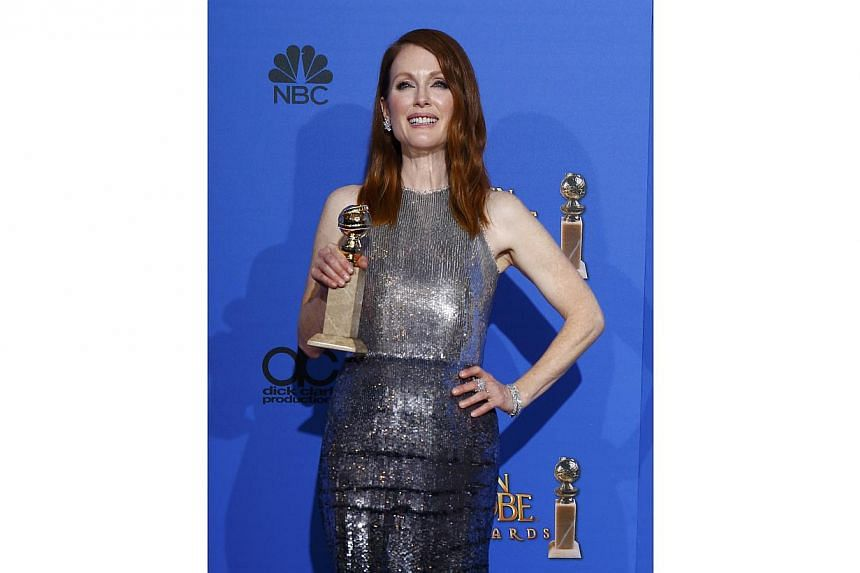Julianne Moore posing with her award for Best Actress in a Motion Picture - Drama for her role in Still Alice at the 72nd Golden Globe Awards in Beverly Hills, California, on Jan 11, 2015. -- PHOTO: REUTERS
