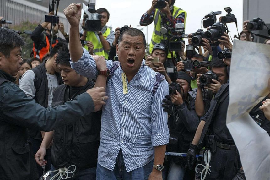 Hong Kong publishing tycoon Jimmy Lai being taken away by police officers at an area previously blocked by pro-democracy supporters, outside the government headquarters in Hong Kong on Dec 11, 2014. -- PHOTO: REUTERS