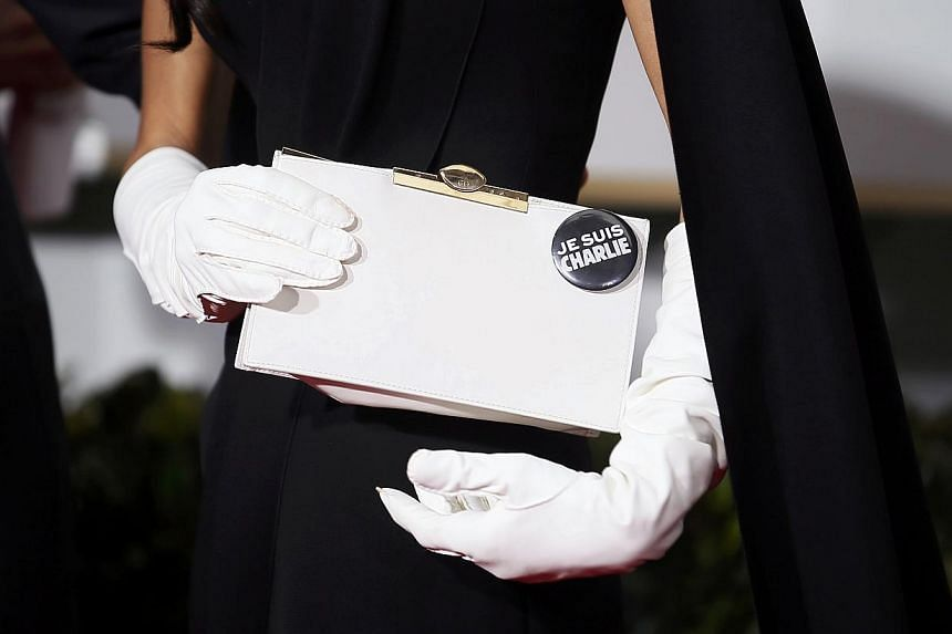 """Amal Clooney wearing a """"Je Suis Charlie"""" button on her purse, with husband George Clooney (not pictured) sporting the same button on his suit at the 72nd Golden Globe Awards on Jan 11, 2015. -- PHOTO: REUTERS"""
