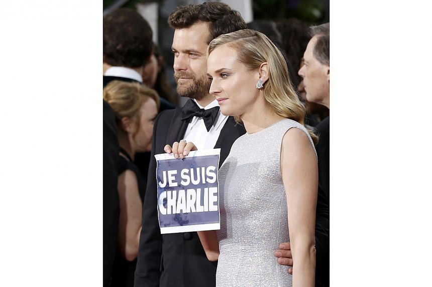 """Actress Diane Kruger holding a """"Je Suis Charlie"""" sign referring to the attacks in Paris as she poses with actor Joshua Jackson at the 72nd Golden Globe Awards on Jan 11, 2015. -- PHOTO: REUTERS"""