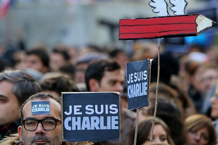 """A man holding a placard that reads""""Je suis Charlie"""" (I am Charlie) during the """"Marche Republicaine"""". -- PHOTO: AFP"""