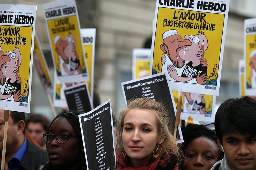 """Spoof Charlie Hebdo front pages titled """"L'amour plus fort que la haine"""" (Love Stronger Than Hatred) were held up in Paris, France, on Jan 11, 2015. -- PHOTO: EPA"""