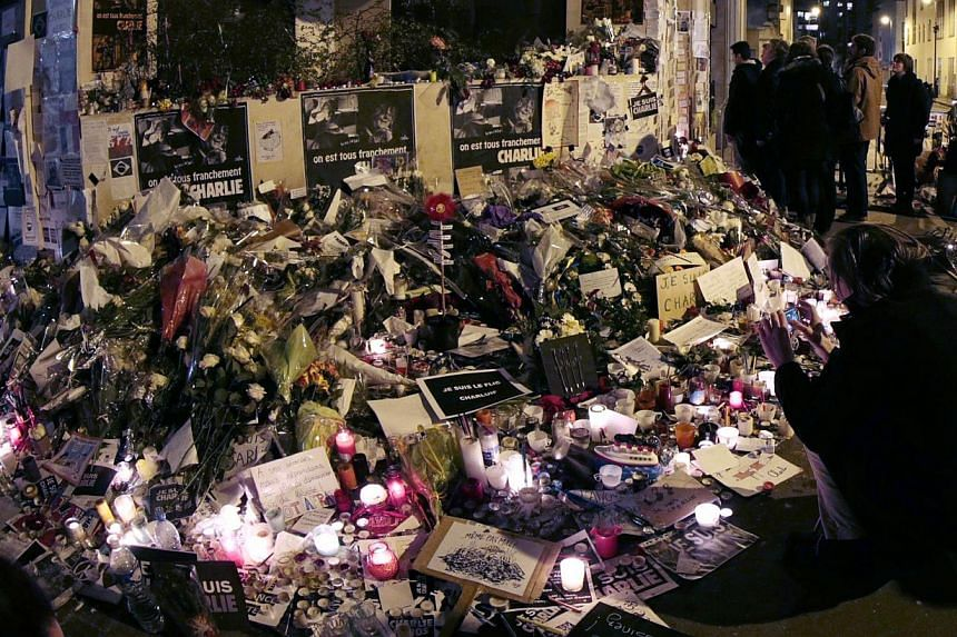 """People visiting a makeshift memorial near the headquarters of Charlie Hebdo at the end of the """"Marche Republicaine"""". -- PHOTO: AFP"""
