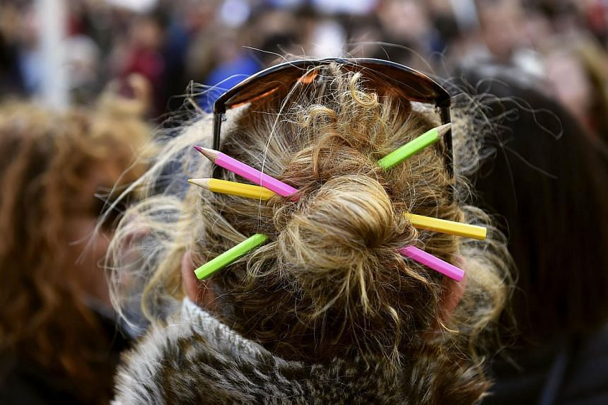 A woman wera pencils in her hair at the old harbour in Marseille, southern France,. -- PHOTO: AFP