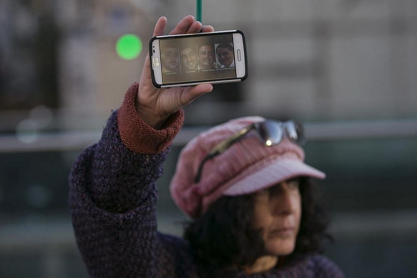 A woman holding up a pencil and her phone displaying pictures of the victims of an attack on a kosher supermarket at Porte de Vincennes near Paris, during a rally in Tel Aviv, on Jan 11, 2015. -- PHOTO: REUTERS