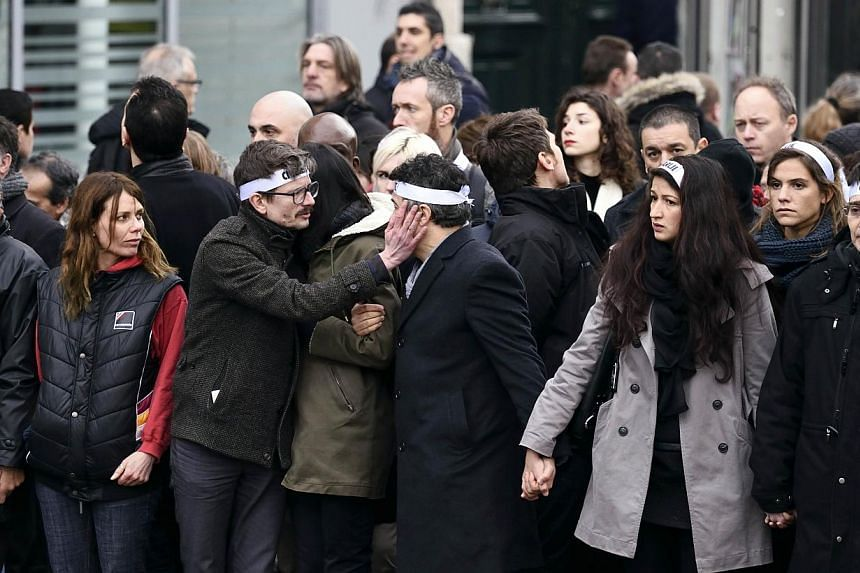 """Members of the Charlie Hebdo satirical magazine looking on as Luz (third from left) touches the cheek of Dr Patrice Pelloux at the """"Marche Republicaine"""". -- PHOTO: AFP"""
