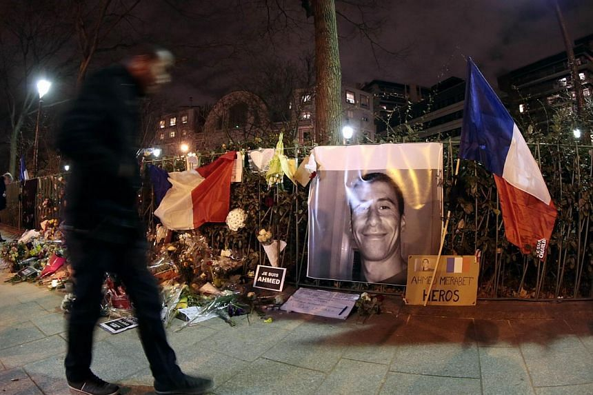 "A makeshift memorial for French policeman Ahmed Merabet near the site where he was shot dead by gunmen close to the headquarters of Charlie Hebdo at the end of the unity rally ""Marche Republicaine"". -- PHOTO: AFP"