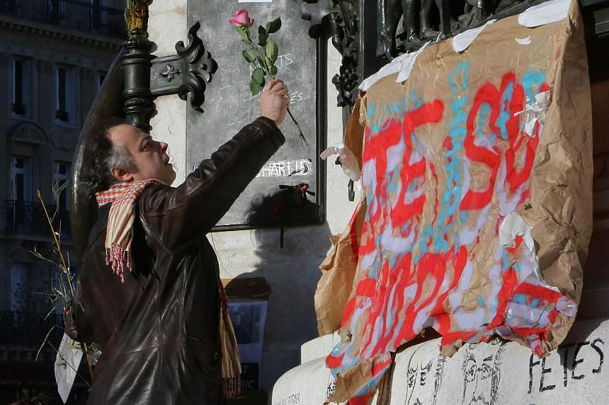 "A man placing a rose as people gather to take part in the ""Marche Republicaine"". -- PHOTO: AFP"