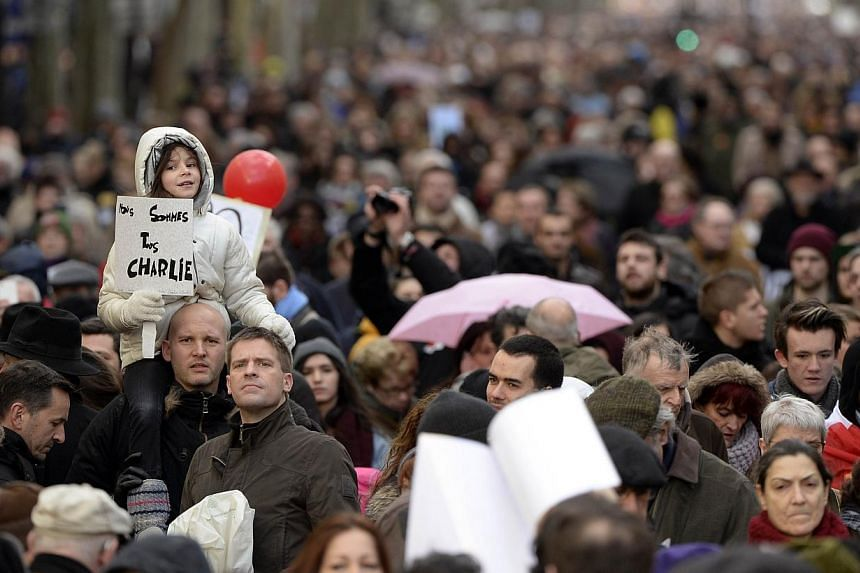 "A girl holding a sign that reads ""Nous sommes tous Charlie"" (We are all Charlie) during the ""Marche Republicaine"" on Jan 11, 2015. -- PHOTO: AFP"
