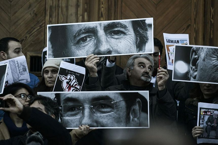 Turkish journalists holding pictures of the late French cartoonists on Istiklal avenue in front of the French consulate during a rally organised by Turkish journalists on Jan 11, 2015, in Istanbul. -- PHOTO: AFP