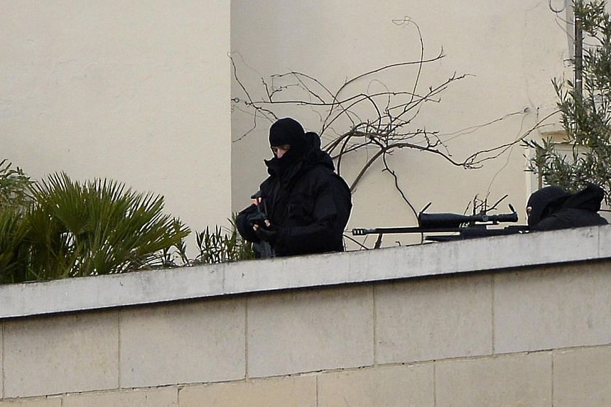 "Police snipers overseeing the ""Marche Republicaine"". -- PHOTO: AFP"