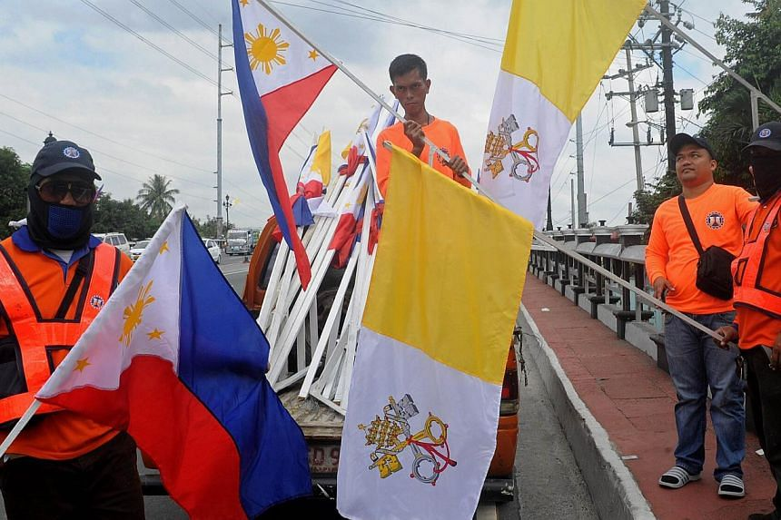 Workers install Philippine and Vatican flags ahead of a visit by Pope Francis in Manila, on Jan 11, 2015. The Pope will immerse himself in some of Asia's most fervent Catholicism during a trip to Sri Lanka and the Philippines starting on Tuesday, wit