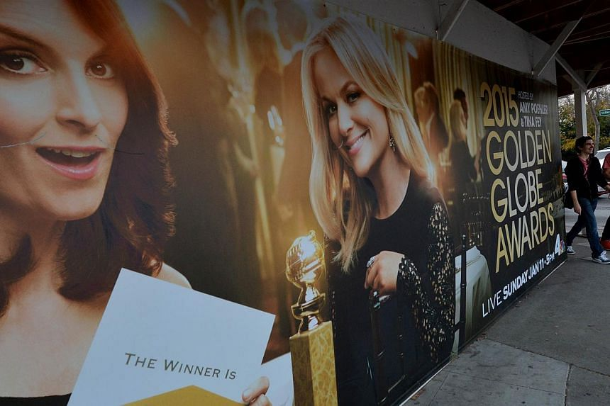 Commuters walk past a poster showing the Golden Globe Award hosts Tina Fey (left) and Amy Poehler (right) in Beverly Hills. The comic duo will present the Globes for a third and final year today in what organizers hope will continue its ratings winni