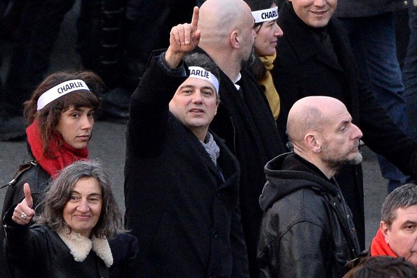 Patrice Pelloux (centre) gestures as he marches with other members of the French satirical weekly Charlie Hebdo and relatives of victims during the Unity rally on January 11, 2015 in Paris in tribute to the 17 victims of a three-day killing spree by