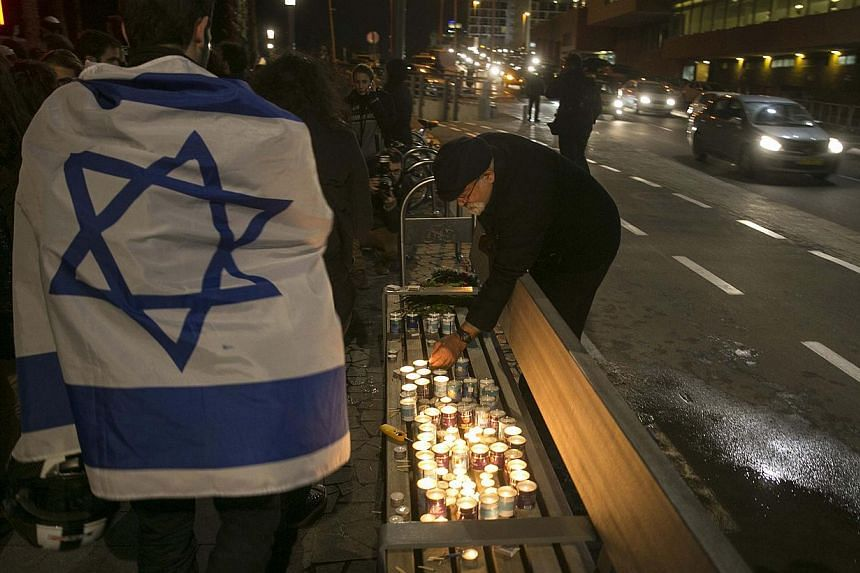 A man lights candles as another draped in an Israeli flag walks by during a tribute for the victims of the shootings at the satirical weekly newspaper Charlie Hebdo and a Jewish deli in Paris, -- PHOTO: REUTERS