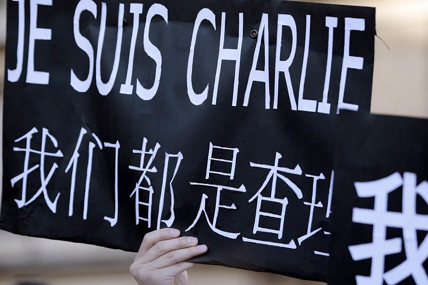 """A protester holds a sign reading """"Je suis Charlie"""" (I am Charlie) - including Chinese characters - during the Unity rally in Paris on January 11, 2015 in Paris in tribute to the 17 victims of a three-day killing spree by homegrown Islamists. - PHOTO:"""
