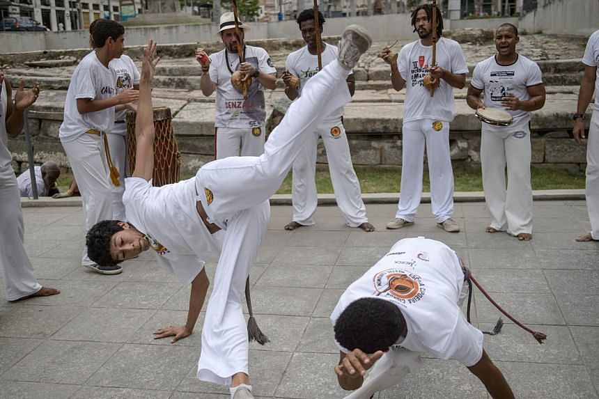 Players of Brazilian Capoeira, a mixture of dance and martial art inherited from the times of slavery, perform to celebrate the nomination of Capoeira to the list of UNESCO's Intangible Cultural Heritage in Rio de Janeiro, Brazil. --PHOTO: AFP