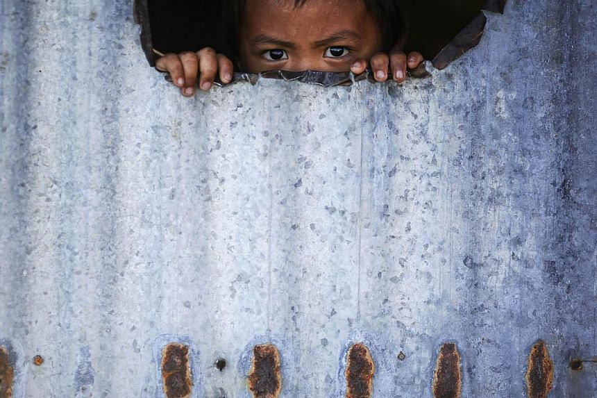A child peers from inside a makeshift house with tin walls Jan 15, 2015, in the coastal part of Tacloban that was destroyed by Typhoon Haiyan. On his first visit to Asia's largest Catholic nation, Pope Francis will visit the central province of Leyte