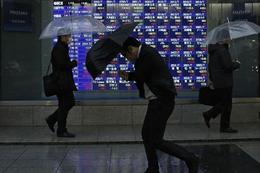 Pedestrians, holding umbrellas, walk past an electronic board showing stock prices outside a brokerage in Tokyo on Jan 15, 2015. -- PHOTO: REUTERS