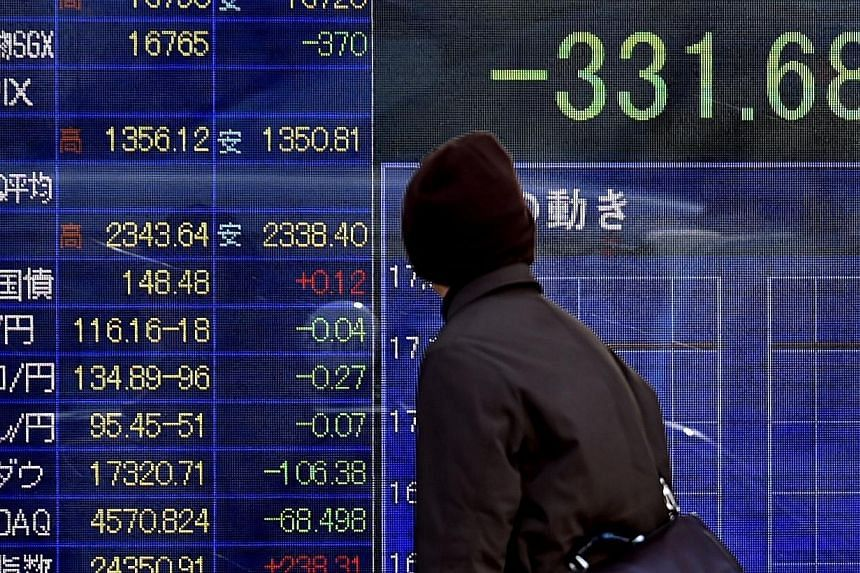 A pedestrian looking at a share prices board in Tokyo on Jan 16, 2015. Asian shares fell on Friday and major currencies mostly stuck to late US levels as investors react to Switzerland's unexpected move to abandon its currency cap. -- PHOTO: AFP
