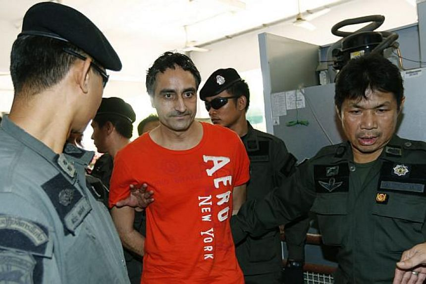 Pakistani terrorism convict Jagtar Singh (second from left) is escorted by Thai police officers into the criminal court in Bangkok, Thailand on Jan 6, 2015. -- PHOTO: EPA