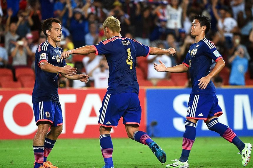 Keisuke Honda (centre) of Japan celebrates with his teammates after scoring the 1-0 lead from the penalty spot during the AFC Asian Cup Group D soccer match between Iraq and Japan in Brisbane, Australia, Jan 16, 2015. -- PHOTO: EPA