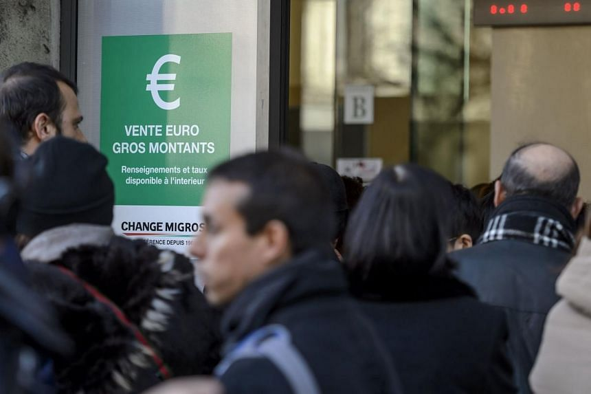 People queue at a bureau de change in Geneva on Jan 15, 2015, after Switzerland's central bank scrapped a policy to artificially hold down the value of the Swiss franc against the euro, sending the franc soaring. Following the announcement, the Swiss