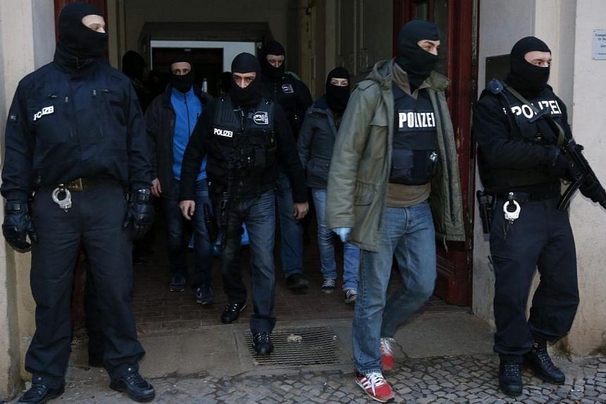 German special police units leave an apartment building in the Wedding district in Berlin on Jan 16, 2015.More than 200 German police officers raided suspected Islamist cells in and around Berlin early on Friday, arresting an alleged leader of